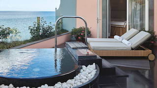 Two sunbeds on a spa balcony next to a jacuzzi overlooking the sea