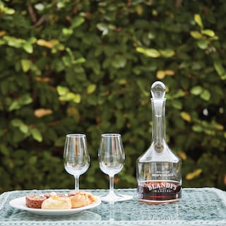 Madeira wine in a glass decanter with two wine glasses and a cake platter on a tray
