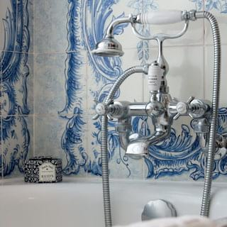 Close-up of silver and porcelain bath taps against blue painted wall tiles