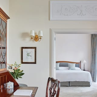 Light and airy hotel suite with an antique writing desk and soft pastel furnishings