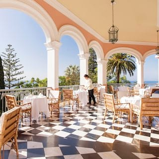 Elegant hotel terrace with checkerboard marble tiles dotted with formal tables