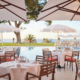 Linen-topped tables under sun umbrellas on a poolside restaurant terrace