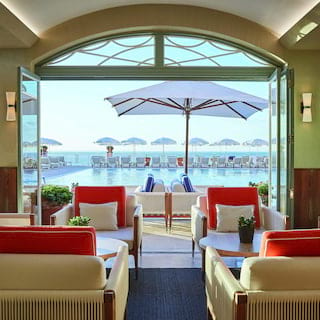 White leather armchairs with red cushions and coffee tables in a poolside restaurant