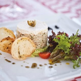 Close-up of a seafood terrine served with garlic bread and a rocket salad