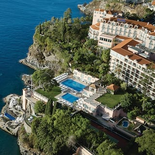 Aerial view of a large hotel building on a lush garden cliff top overlooking the sea