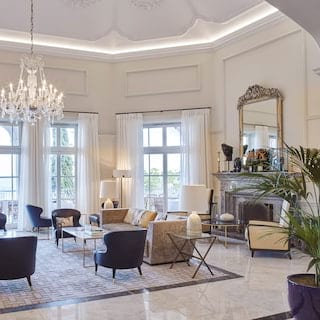 Spacious hotel lobby with a crystal chandelier and monochrome soft furnishings