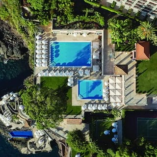 Birds-eye-view of three outdoor hotel pools set within lush clifftop gardens