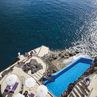 Birds-eye-view of an outdoor sea pool surrounded by tiered terraces next to the ocean