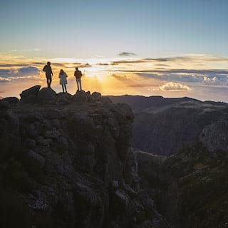 Silhouette of three people standing at a mountaintop above the clouds at sunrise