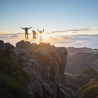 Silhouette of three people jumping into the air on a mountain top at sunrise
