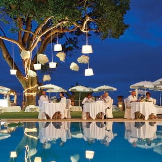Guests in white at formal dining tables lit by hanging lanterns next to an outdoor pool