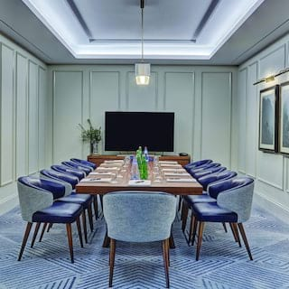 Wood-panelled room with blue leather chairs and a table set for a meeting s