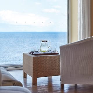 Glass jug of water on a rattan coffee table next to a large window with sea views