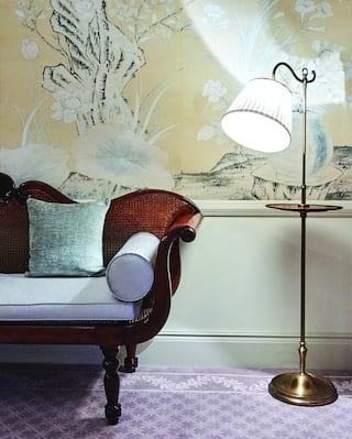 Close-up of a mahogany chaise longue with powder blue cushions next to a lamp