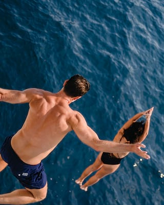 Couple leaping into a deep blue ocean