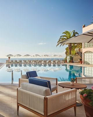 Comfy armchairs with blue cushions around an outdoor hotel pool under blue skies