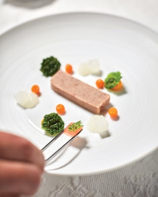 Close up of garnish being placed on a pâte starter dish