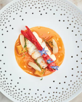 Birds-eye-view of a shrimp dish topped with edible flowers in a white ceramic bowl