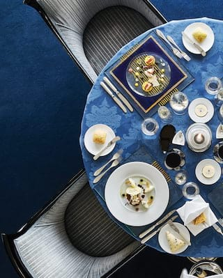 Circular table topped with a blue-patterned tablecloth and formal dinner settings