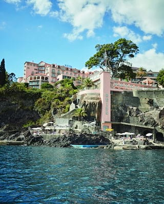 Pink facade of a Victorian hotel spread across a cliff side overlooking the sea