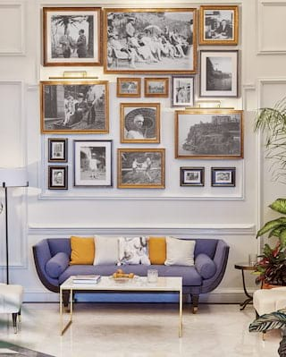 Modern blue sofa with yellow cushions under a gallery wall of old photos