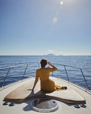 Lady in a yellow dress sitting on the bow of a sailing boat heading towards islands
