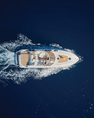 Birds-eye-view of a luxurious small yacht sailing across deep blue waters