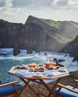 Close-up of breakfast on an outdoor table overlooking the coast