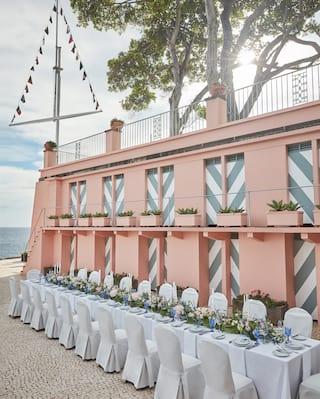 Wedding banquet table with a pink floral centerpiece on a cobblestone patio