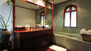 Spacious bathroom with curved corner bath, wooden floors and jade accents