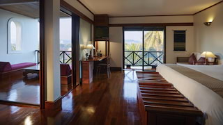 Spacious hotel room with gleaming polished wood floors and a balcony