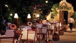 Row of outdoor restaurant tables in evening light surrounded by gardens