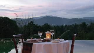 Circular candlelit table set for two, overlooking a mountain at sunset