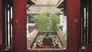 Oriental courtyard lily pond with bamboo plants and flickering candles