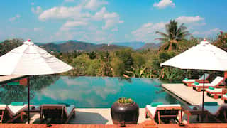 Infinity pool under sunny skies overlooking a jungle and distant mountains