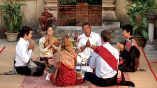 Six people sitting in a circle for a baci ceremony in an oriental courtyard