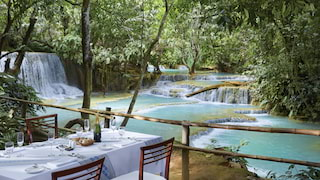 Dining table overlooking the turquoise water of the Kuang Si falls