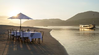 Banquet table on an empty beach at sunset with a river boat gliding nearby