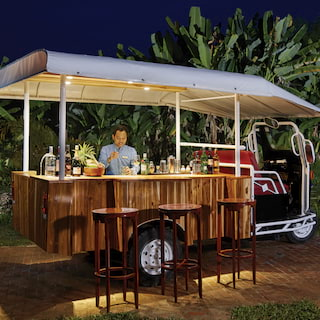 Tuk tuk converted into a bar with wooden bar top and cocktail paraphernalia