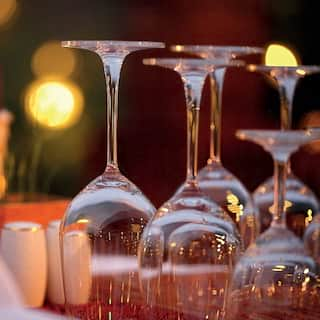 Close-up of restaurant table with upturned wine glasses reflecting light