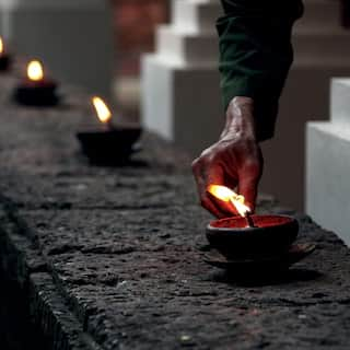 A row of candles being lit along the stone wall of a raised lily pond