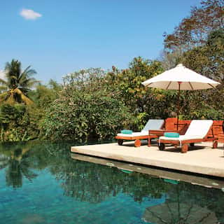 Infinity pool with two sunbeds and parasol on a poolside surrounded gardens