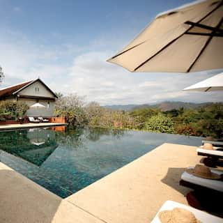 Outdoor infinity pool and U-shaped poolside with rows of sunbeds