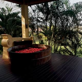 Outdoor barrel bath with floating red flowers on an open-air terrace