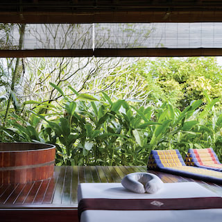 An open-air terrace with two sun beds and barrel soaking tub