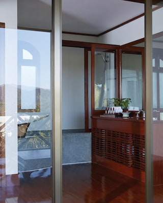 View through glass doors of a hotel bathroom with a teak-wood cabinet