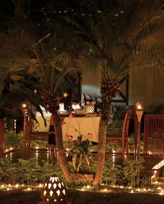 Private dinner table among gardens, surrounded by candles