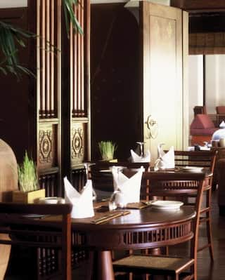 Row of circular tables with white linen napkins in an elegant restaurant