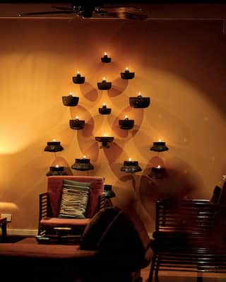 Lamp-lit hotel lobby with peach tones and wall-candles in a leaf formation