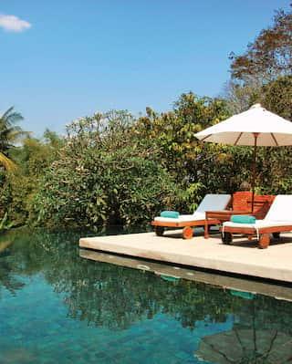 Hotel infinity pool overlooking jungle-coated Laotian mountains